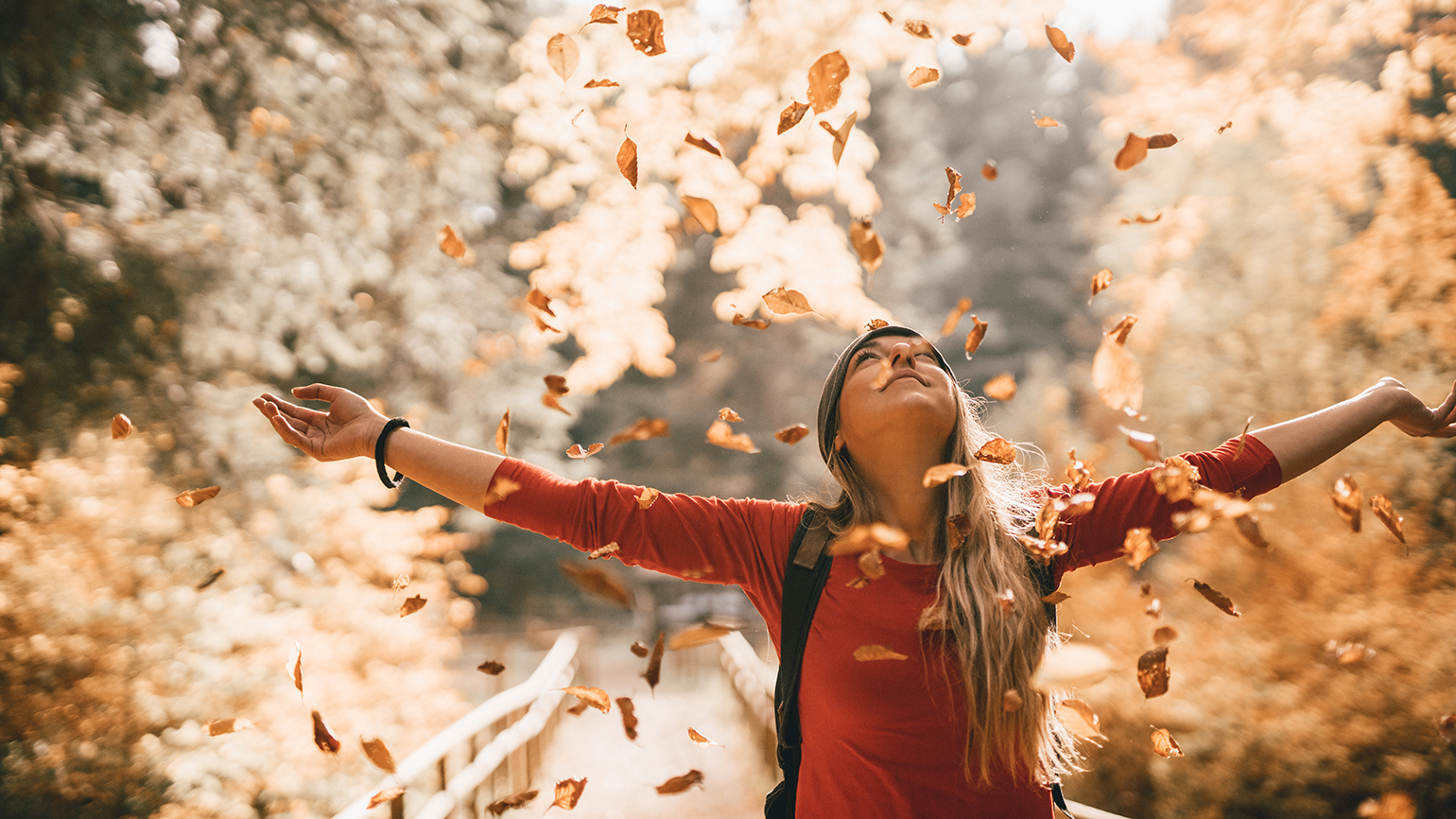 A woman stands, arms outstretched, in the falling leaves of autumn