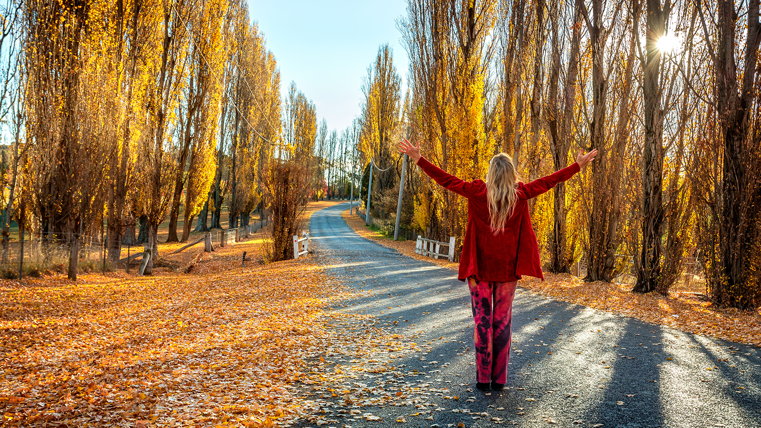A woman raises her arms in gratitude on a country road in autumn