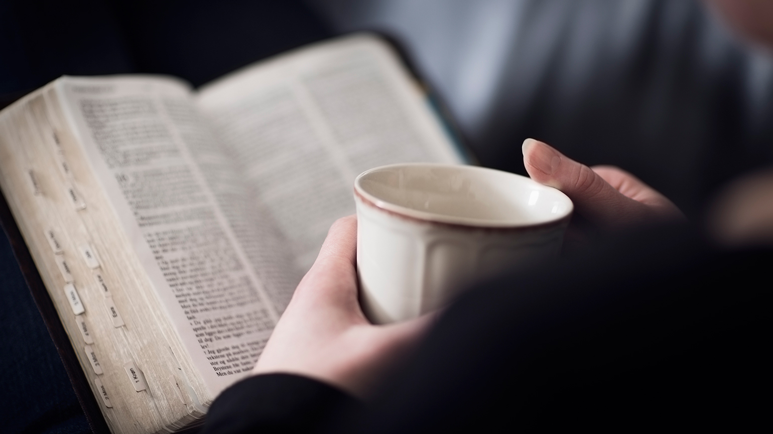 A woman holds a cup of coffee with an open Bible in her lap