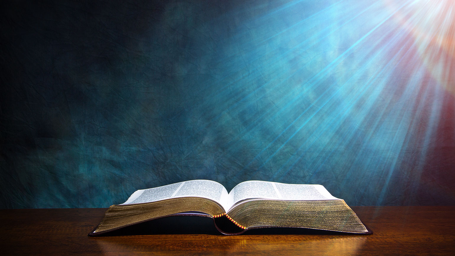 A heavenly light shines down on an open Bible