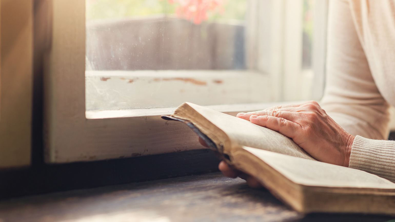 A woman reads her Bible while seated by a window where the sun shines in
