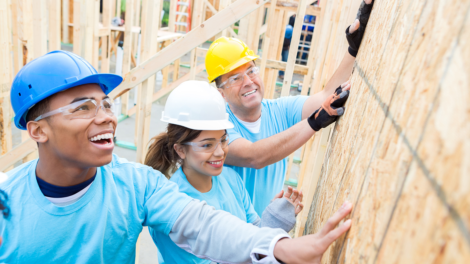 Volunteers erect a house for charity