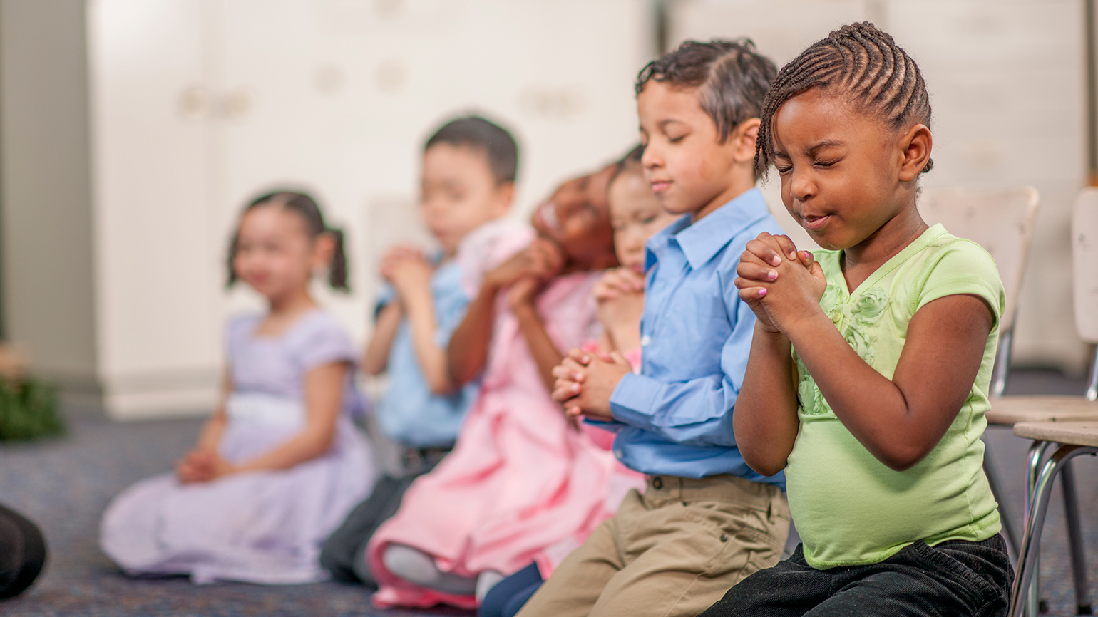 A group of young children kneel, hands clasped in prayer