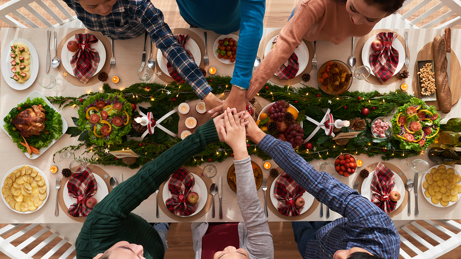 A family clasps hands at Christmas