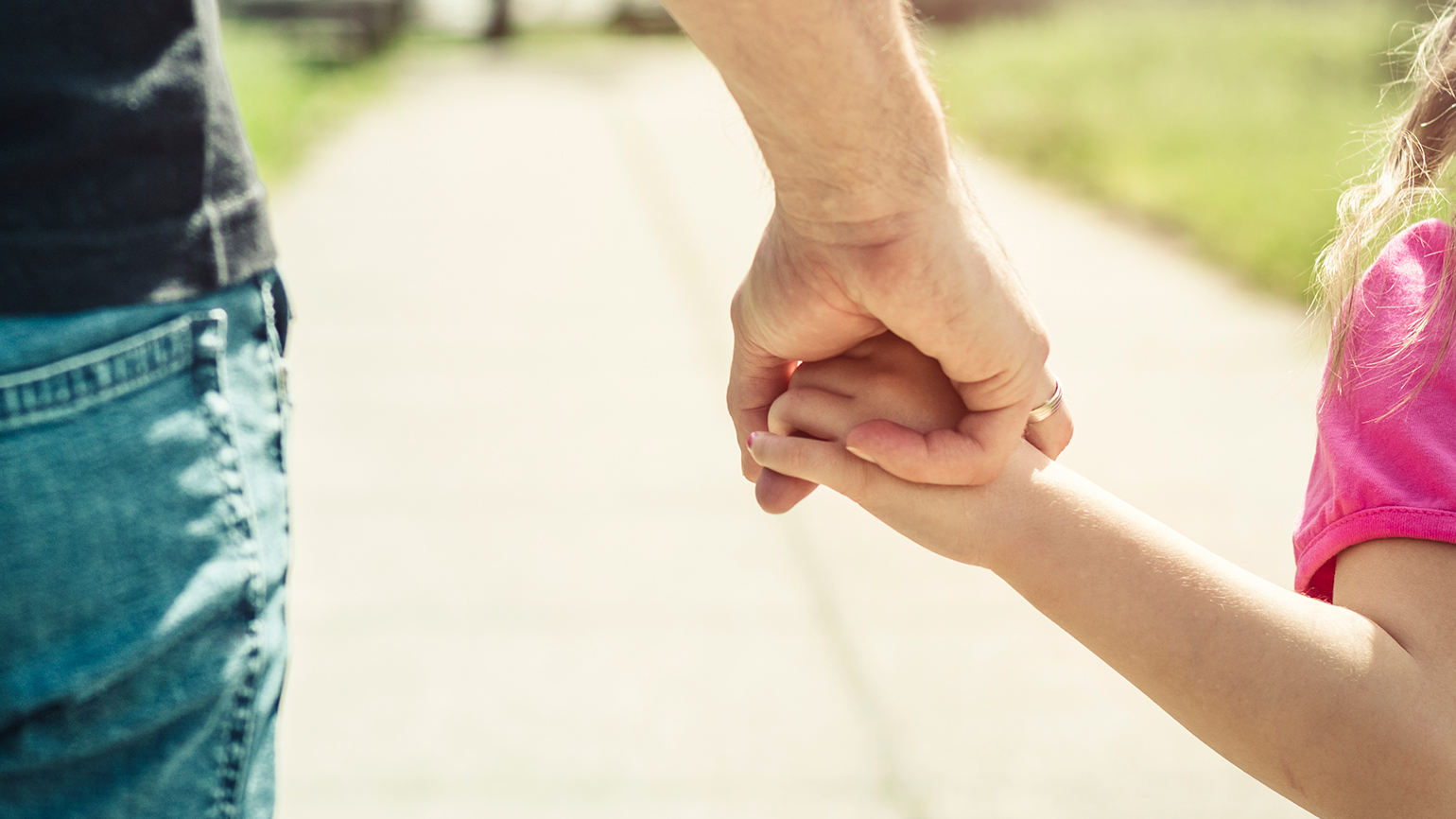 A fauther and young daughter hold hands