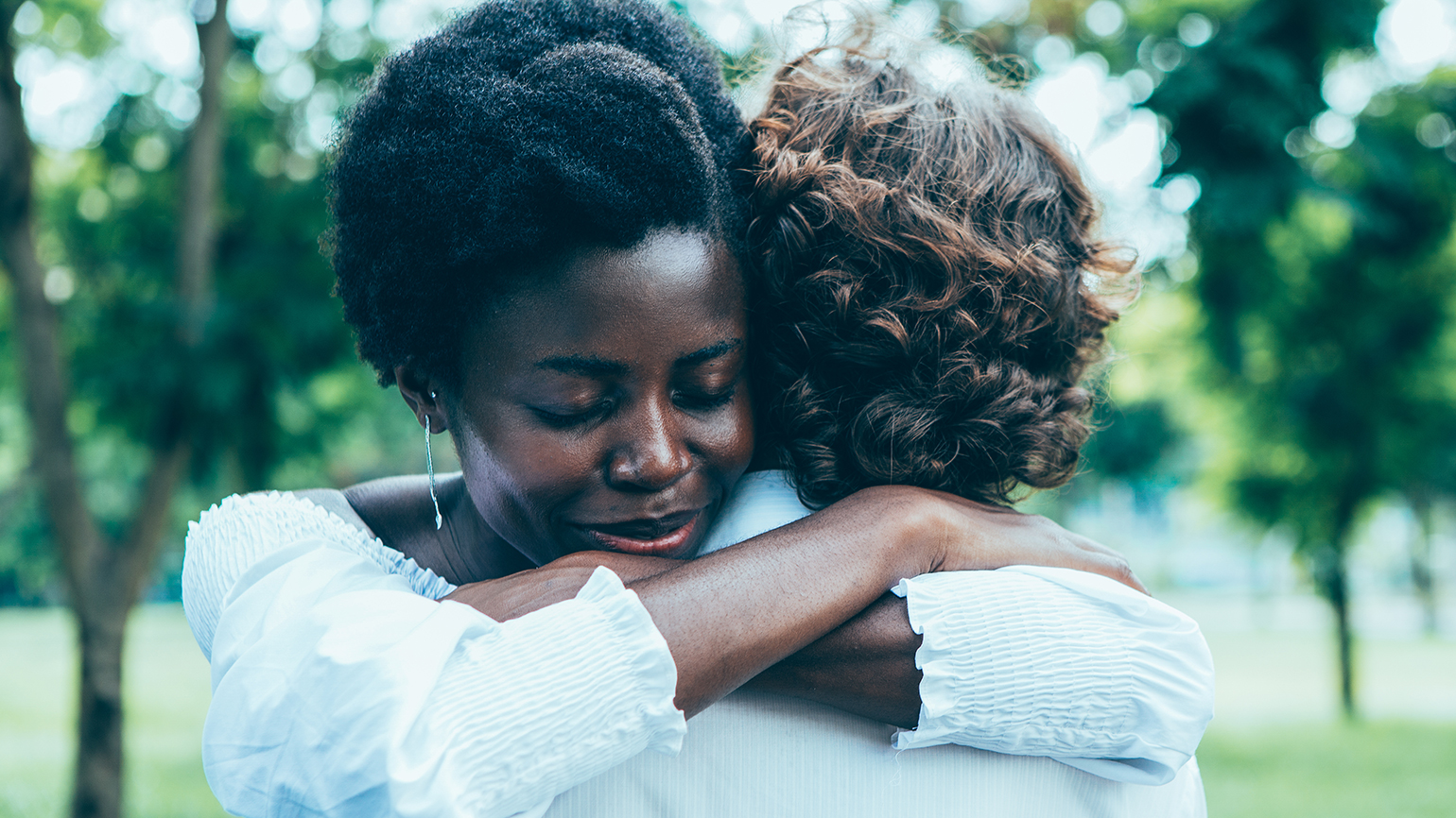 Two women engage in a forigiving hug