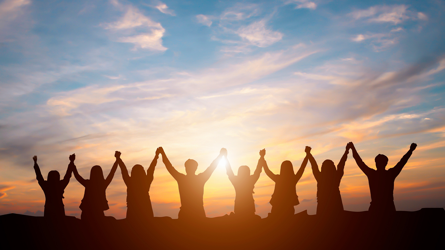A group of friends raise their arms in gratitude and praise