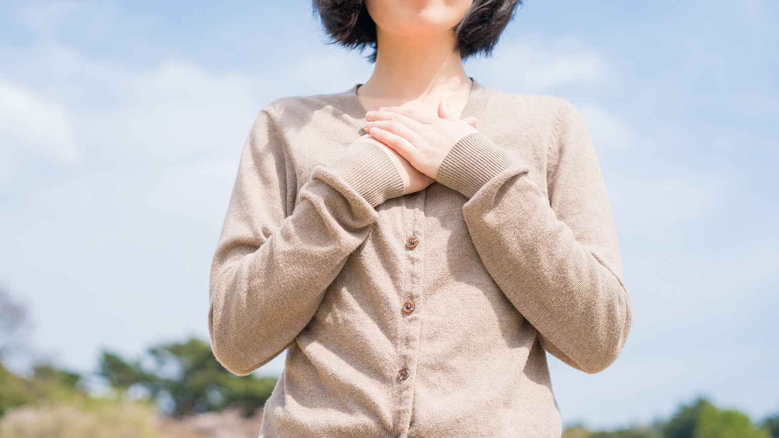 A woman clasps her hands to her heart in gratitude