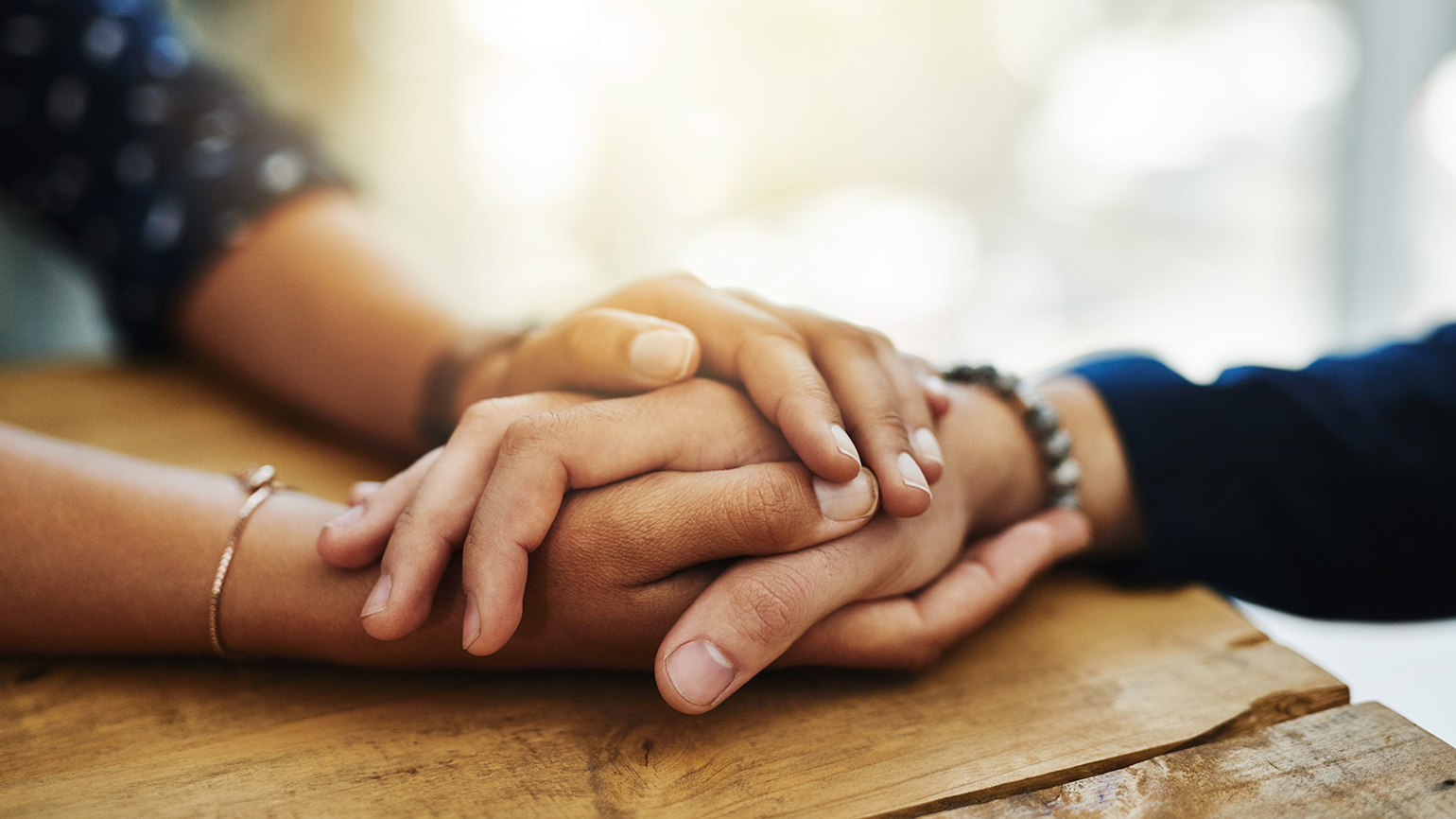 A caregiver clasps her charge's hand in hers