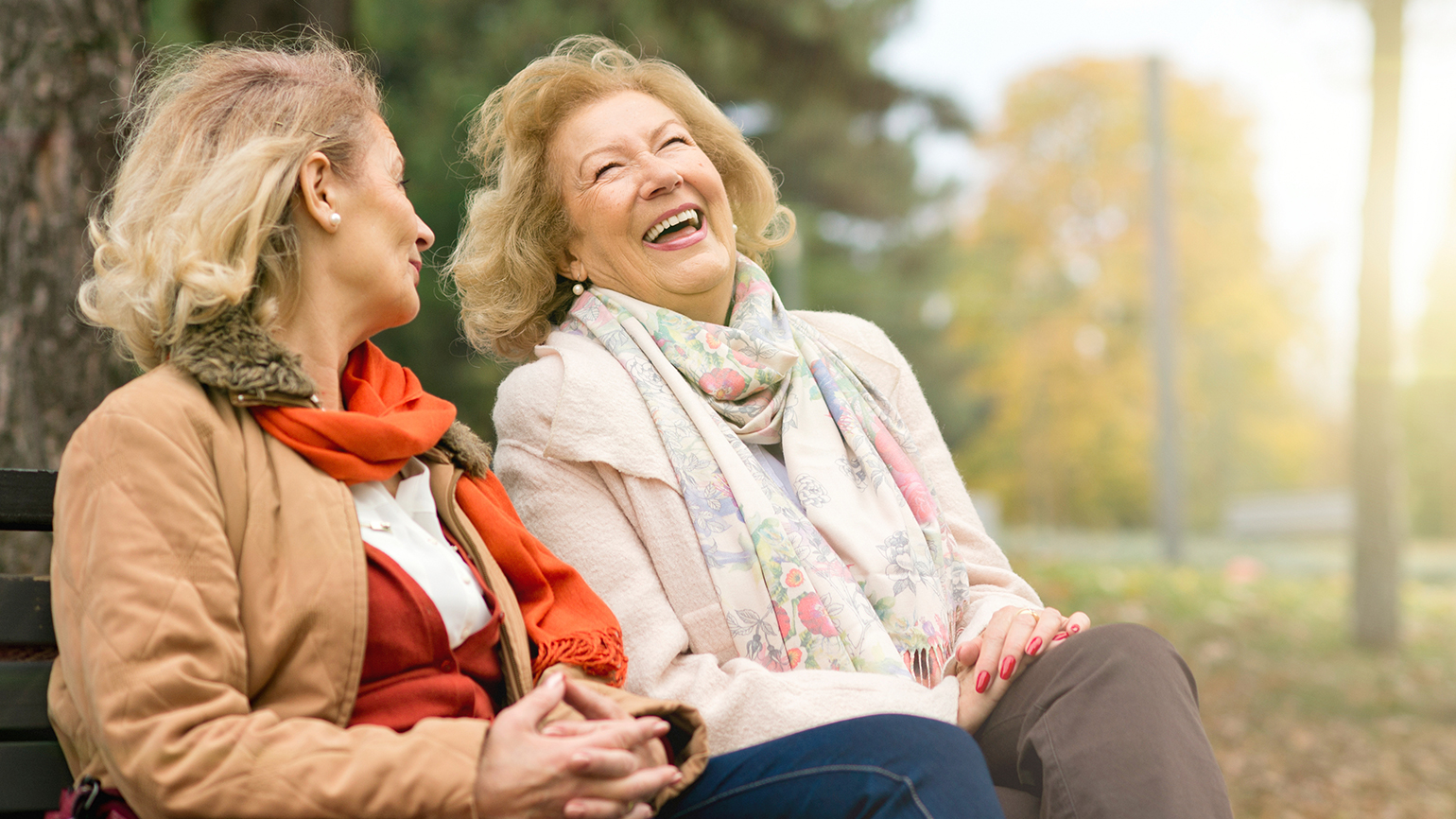 Women laughing on an outside bench