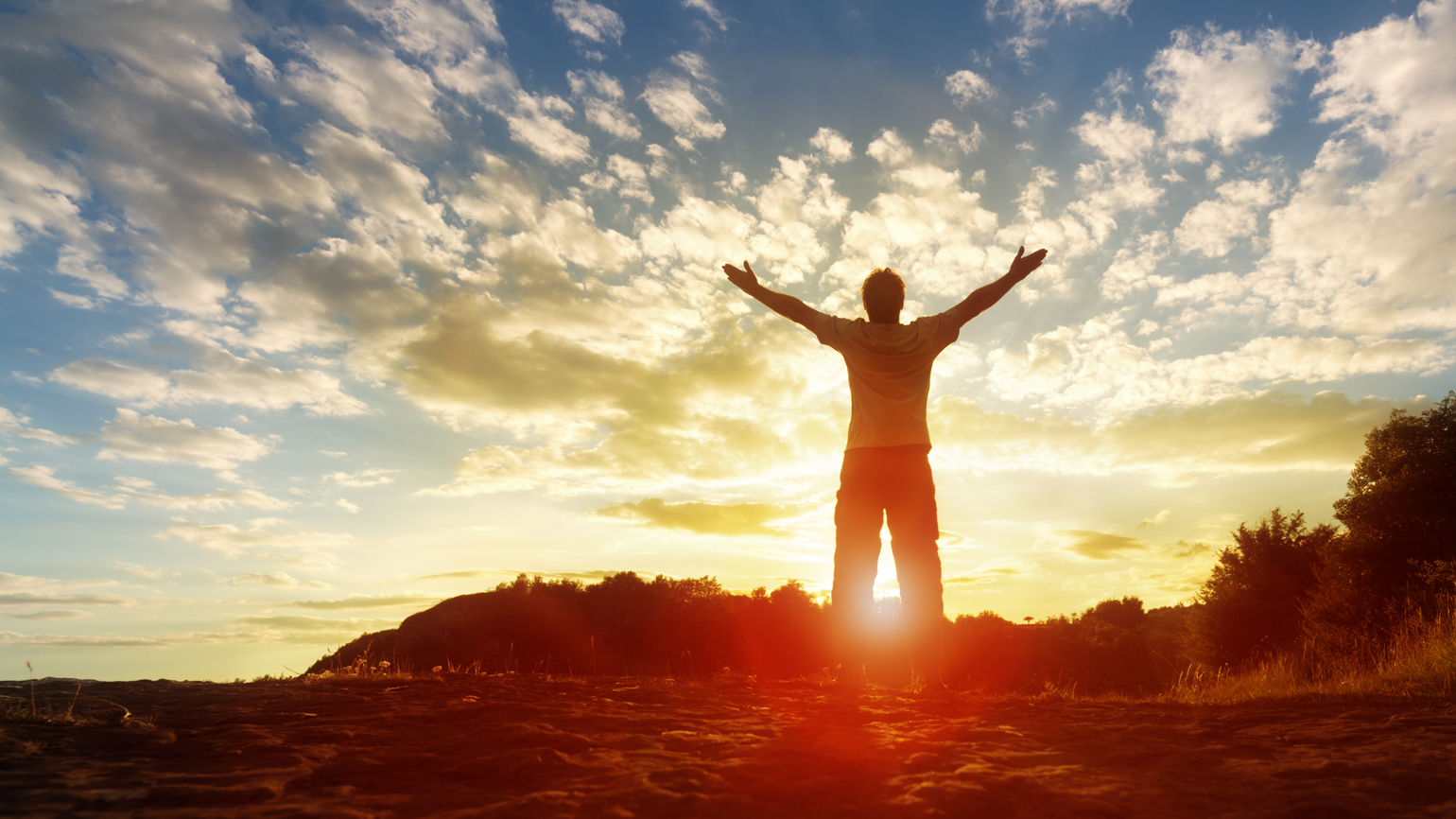 A man greets the sunrise, his arms outstretched