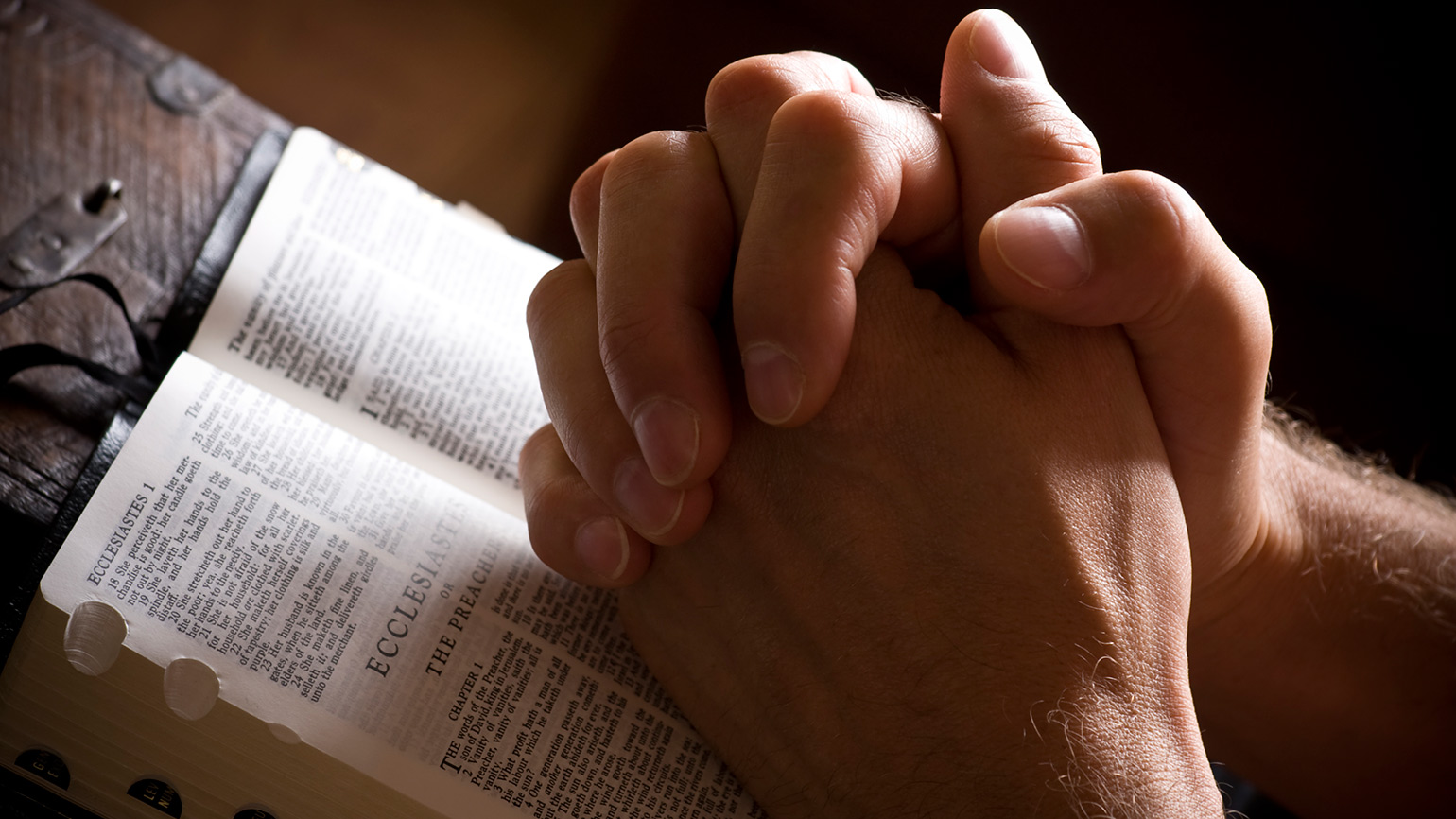 A mans hands, clasped in prayer, rest on a Bible
