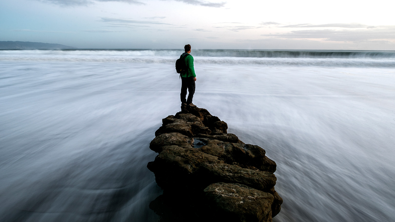 A man stands atop a boulder while water rushes by on both sides