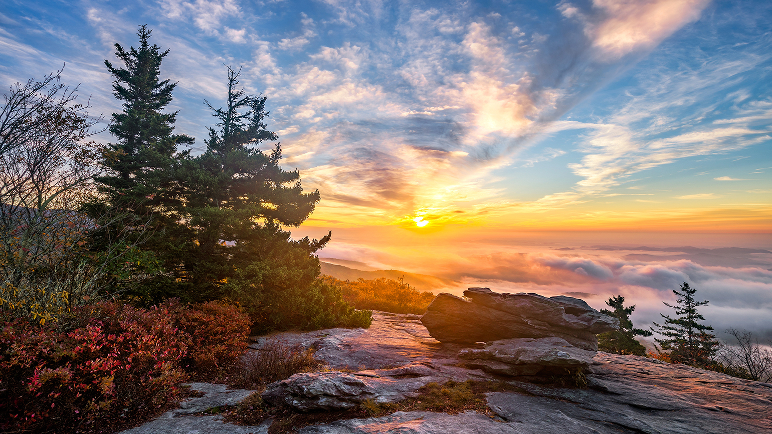 The sun rises over mountains and evergreen trees