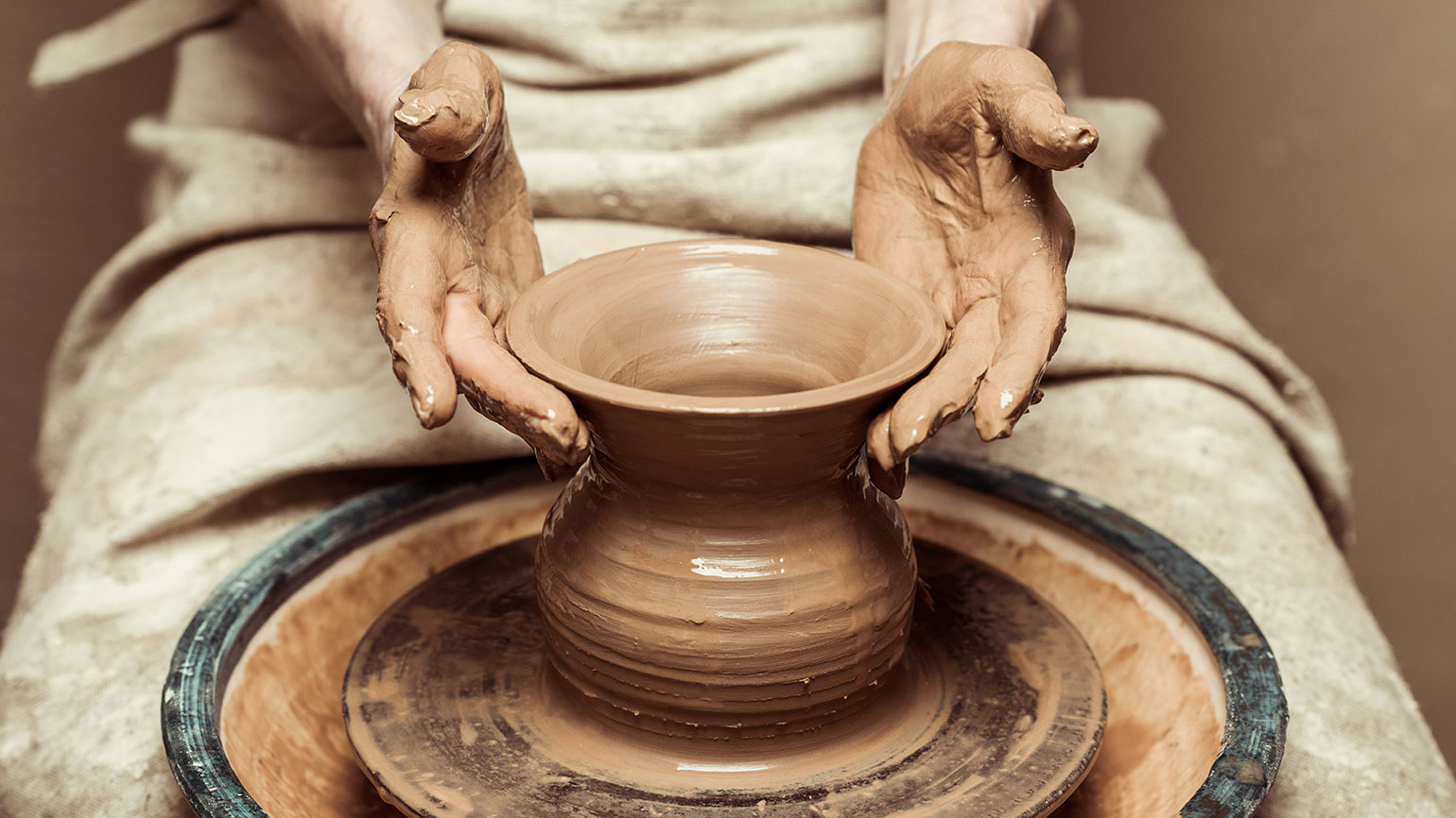 A woman's hands throwing a vase on a pottery wheel