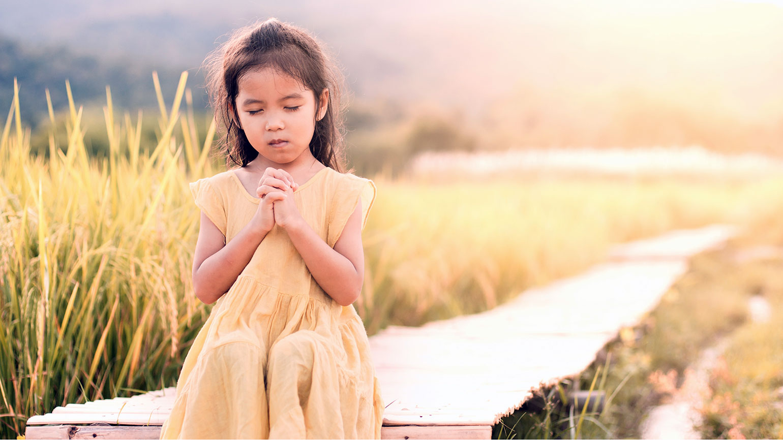 A young girl prays outdoors