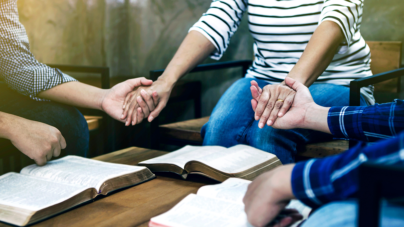 A group of worshippers clasp hands in prayer