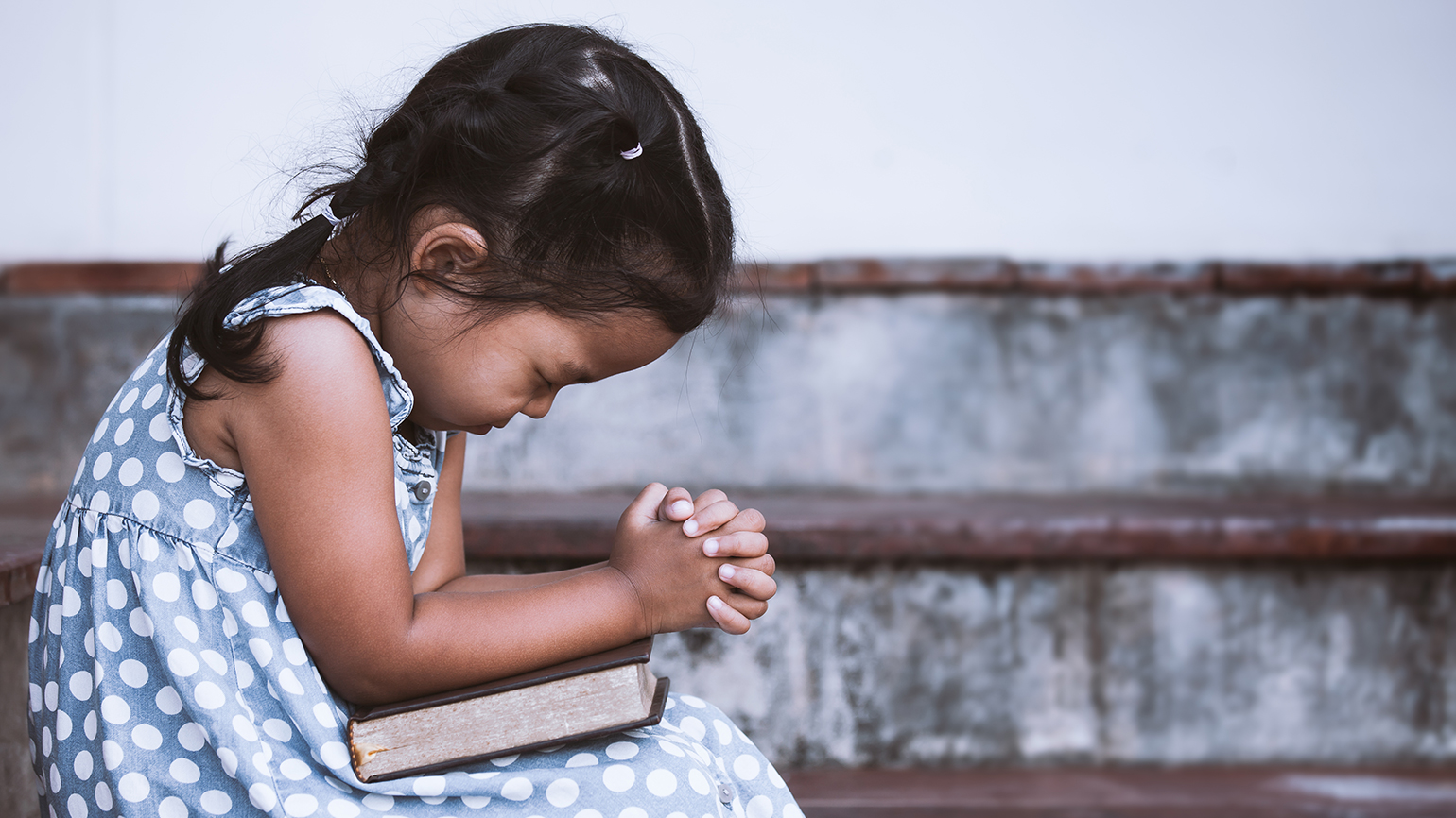 A young girl bows her head in prayer