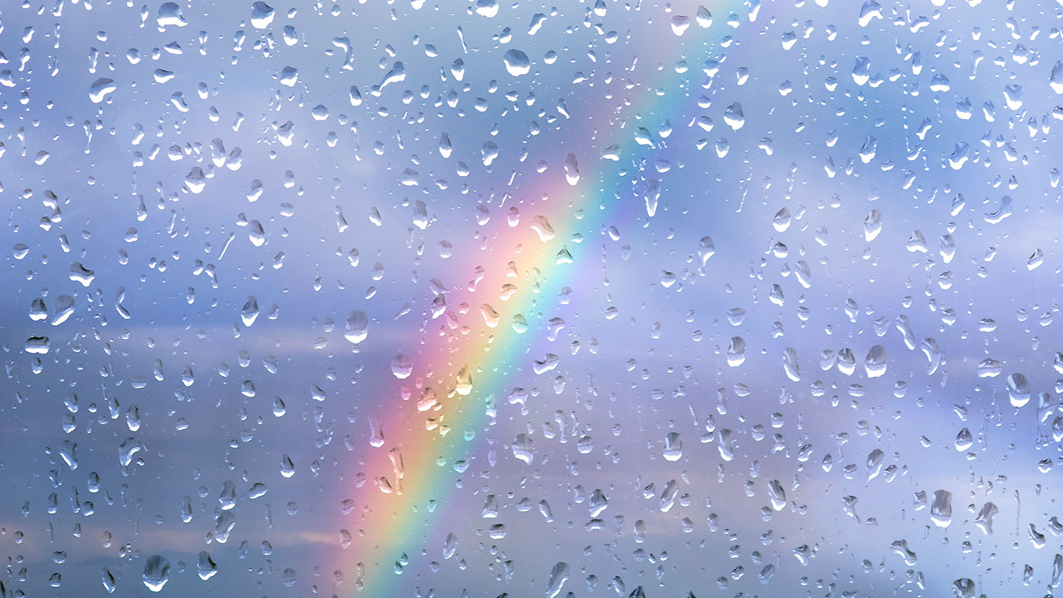 A rainbow is viewed through a window with raindrops beaded up on it