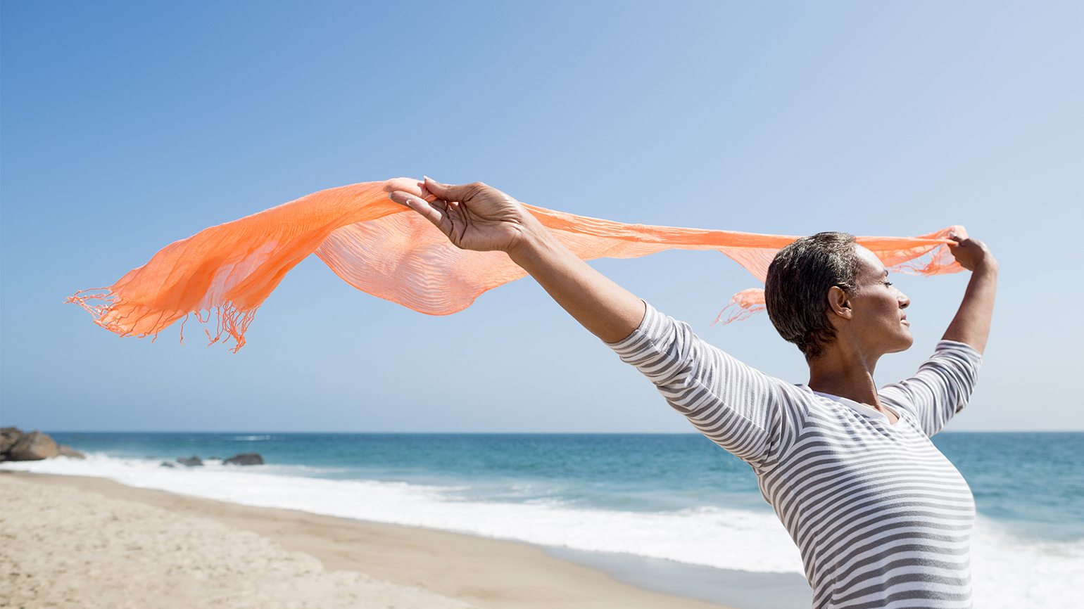 A woman on a beach lets her scarf wave in the breeze