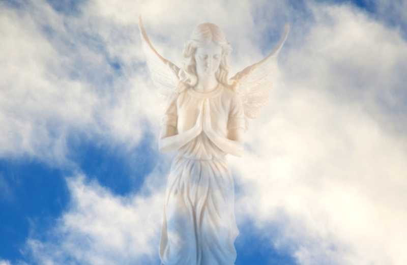 A photo composite of an angel statue against a blue sky with clouds.