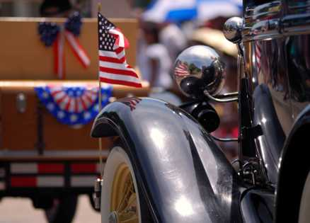 Flag-festooned antique cars in a Memorial Day parade