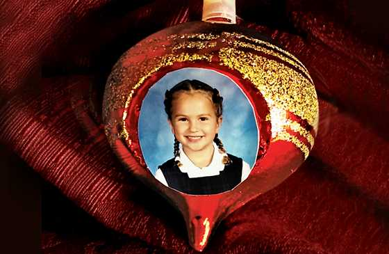 A red Christmas ornament with gold glitter and Micaela's kindergarten picture