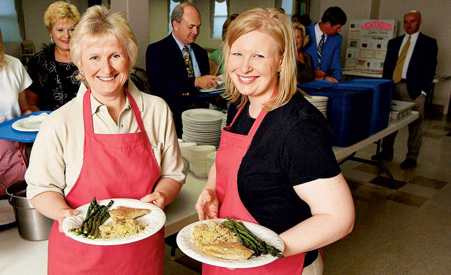 Jackie and Diane in aprons at a healthy church supper