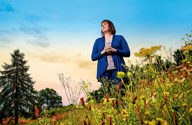 Susan Call standing in a field of flowers
