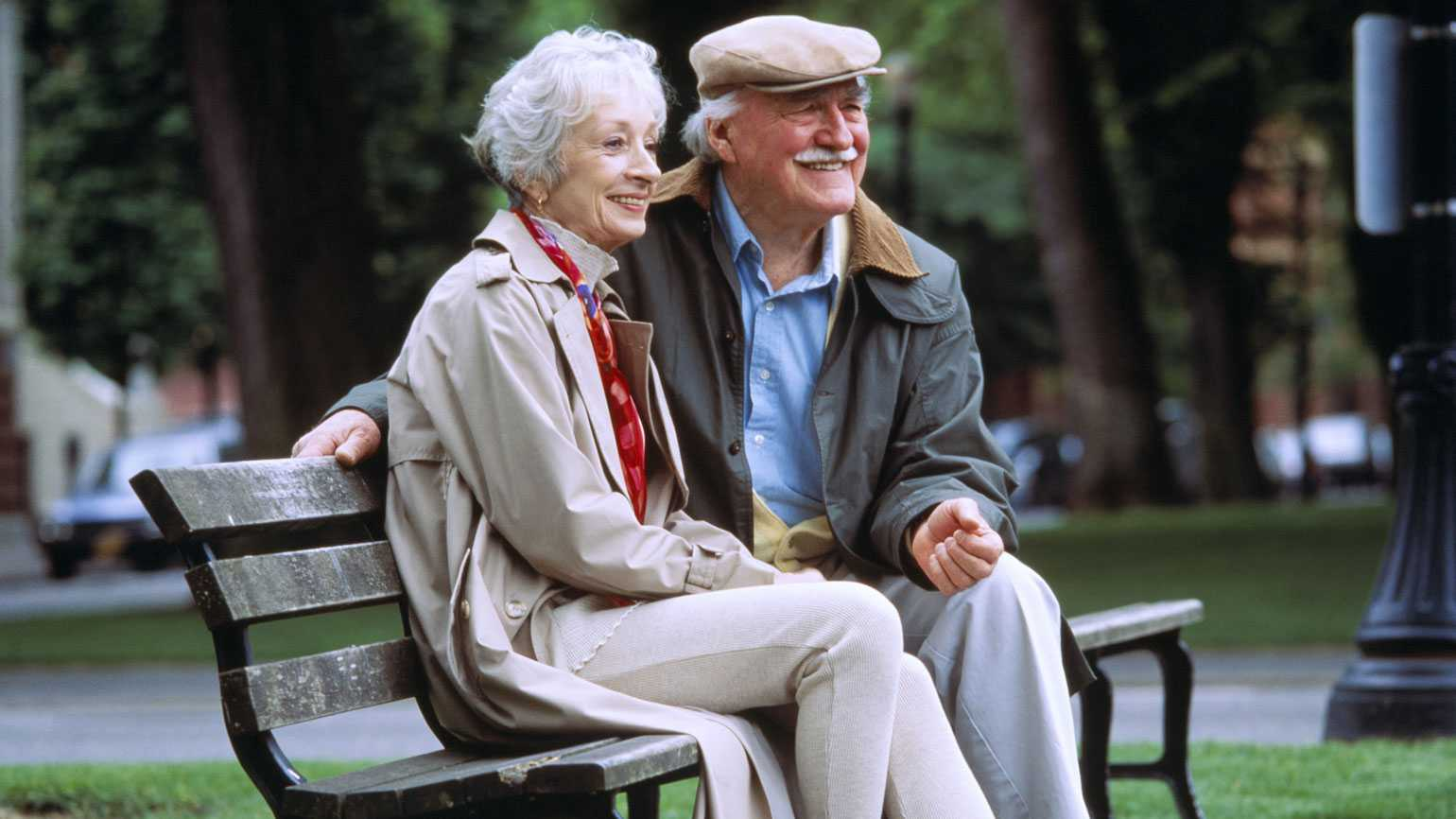 A mature couple enjoy an outing in the park.