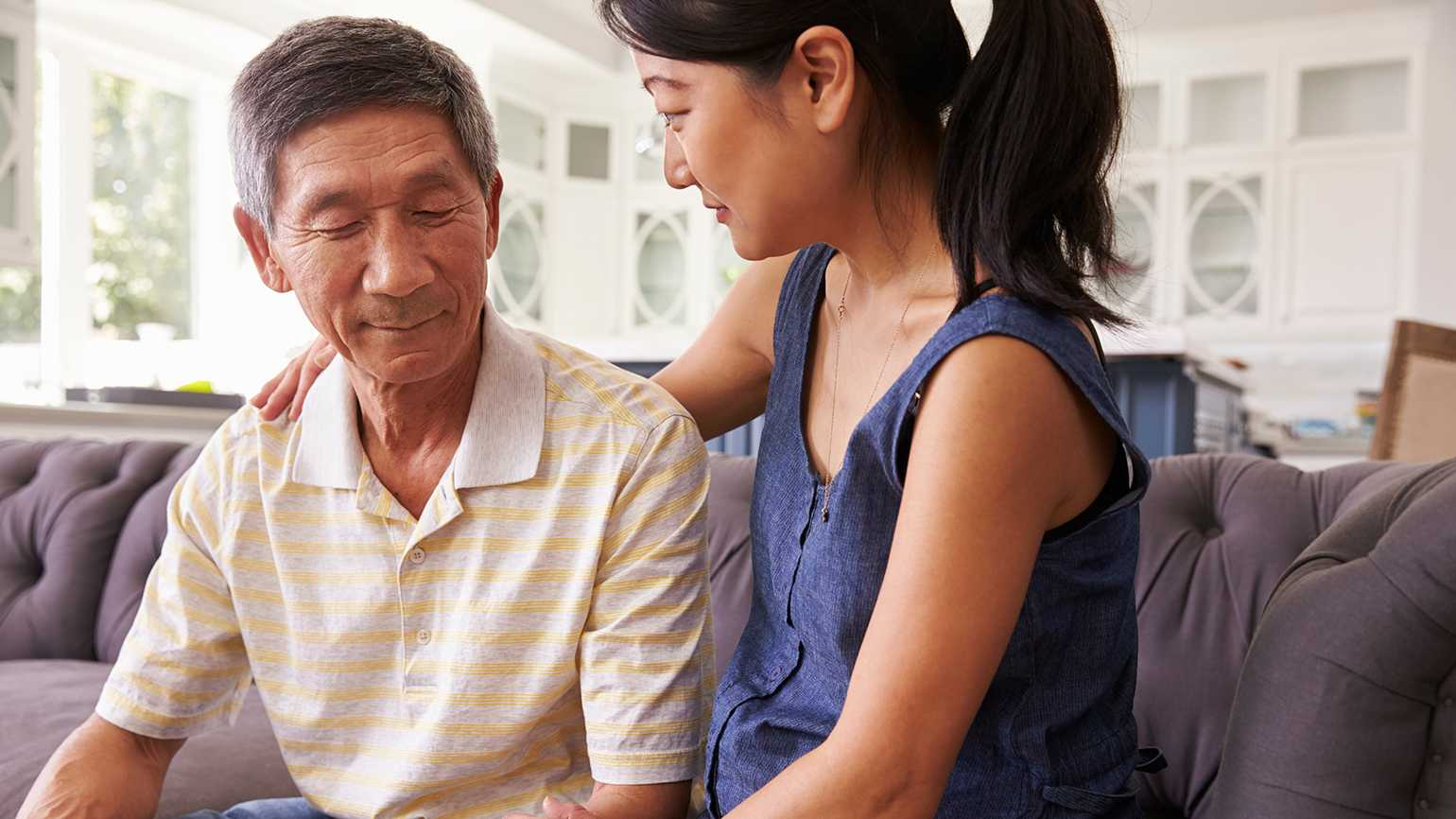 An adult daughter comforts her father who is dealing with dementia