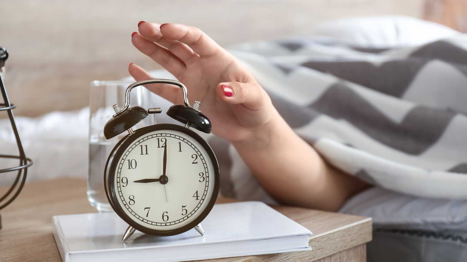 A woman reaching for her alarm clock; Getty Images