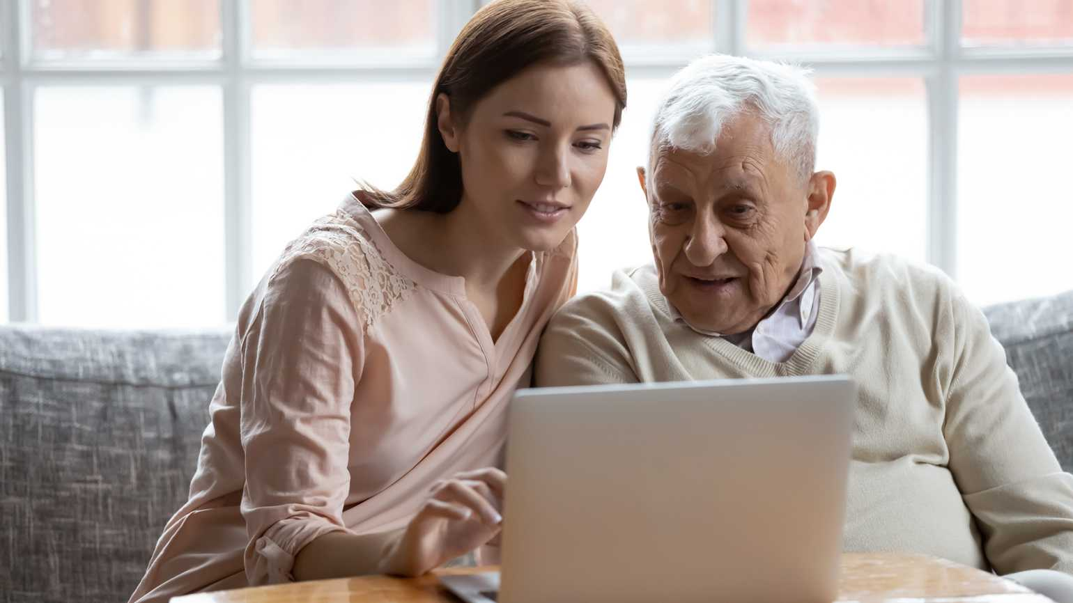 A woman teaching a senior man to use a laptop; Getty Images