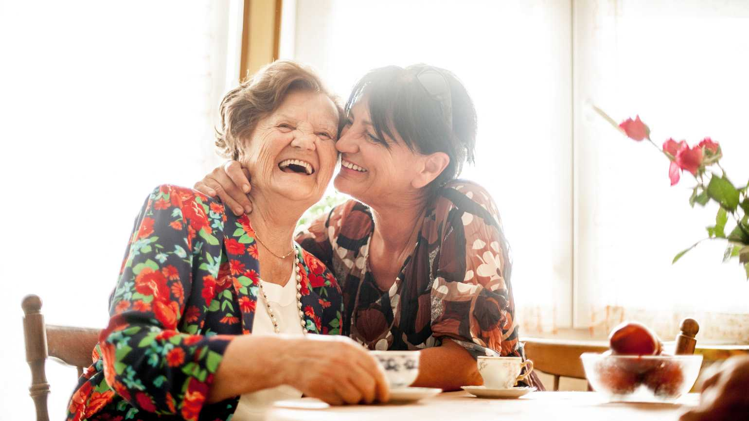A daughter taking care of her mother while having a laugh.