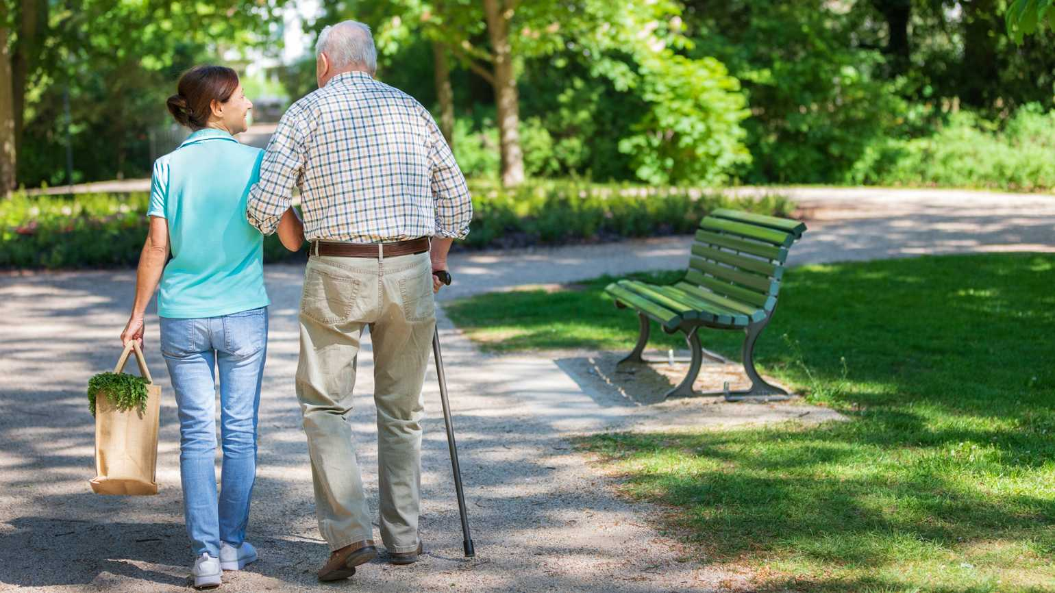 A caregiver woman with a senior man walking in the park.