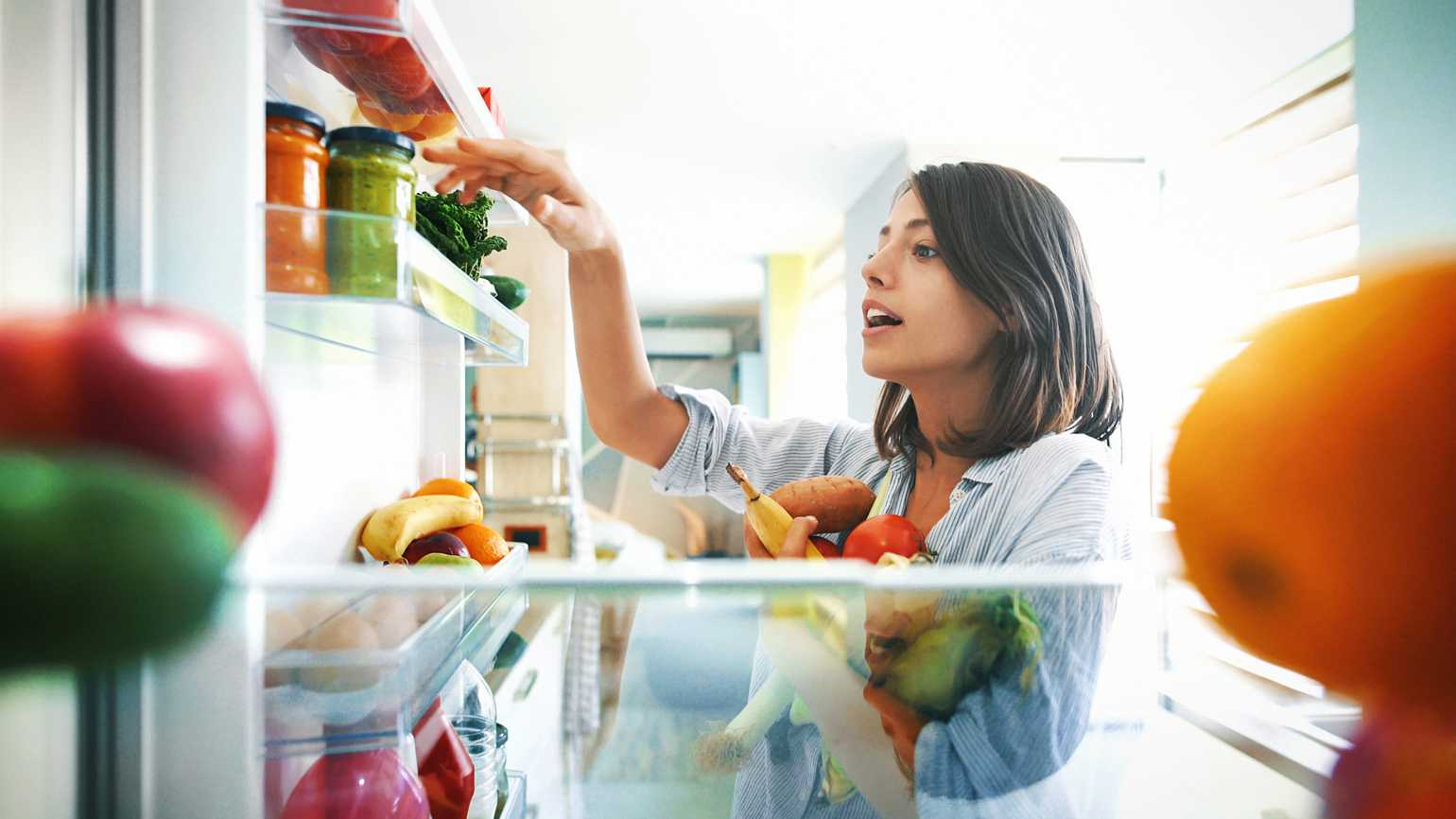 A woman sorting out her fridge with healthy foods.