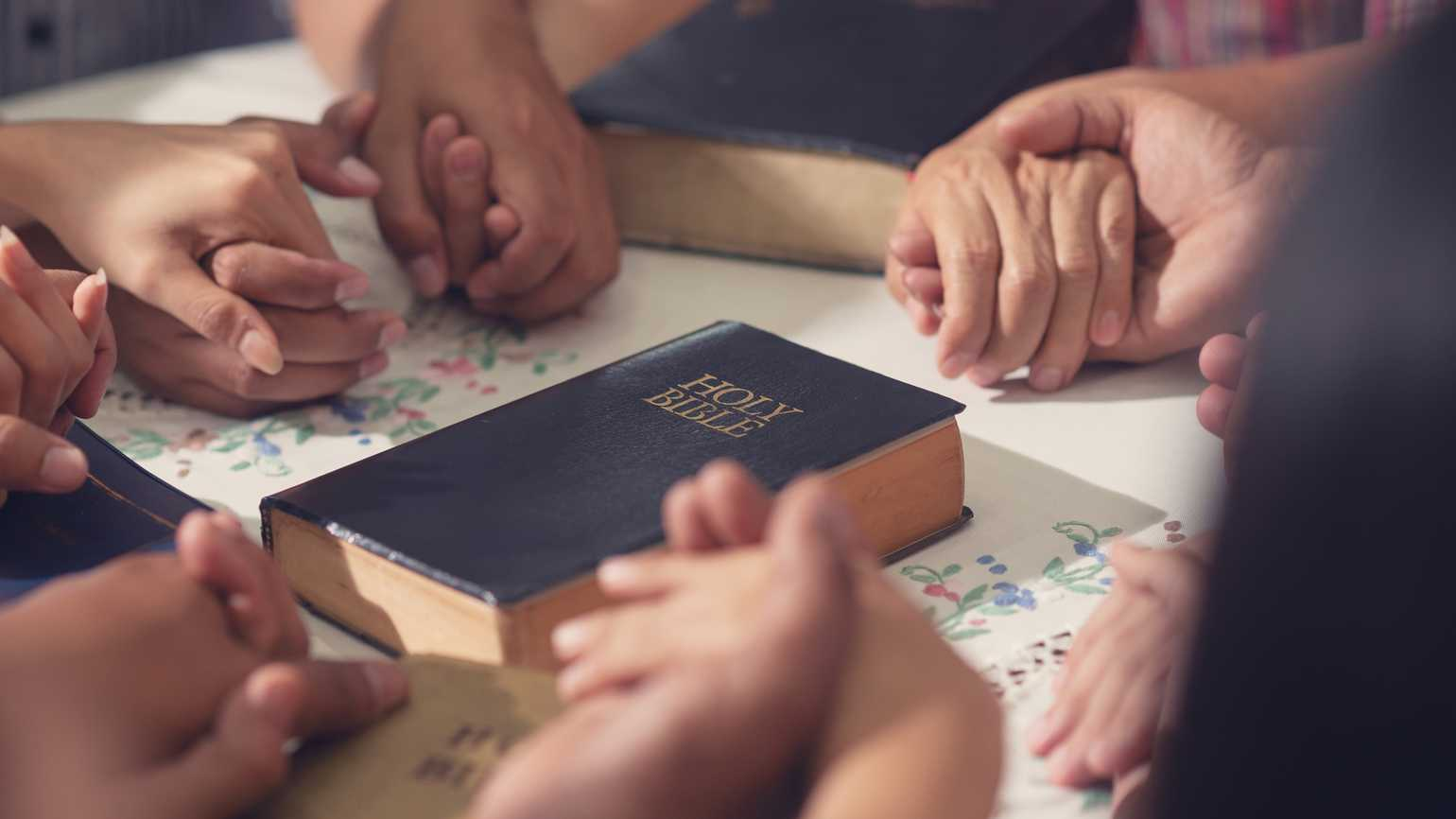 A Bible study group holding hands as a Bible rests in the center of the table.