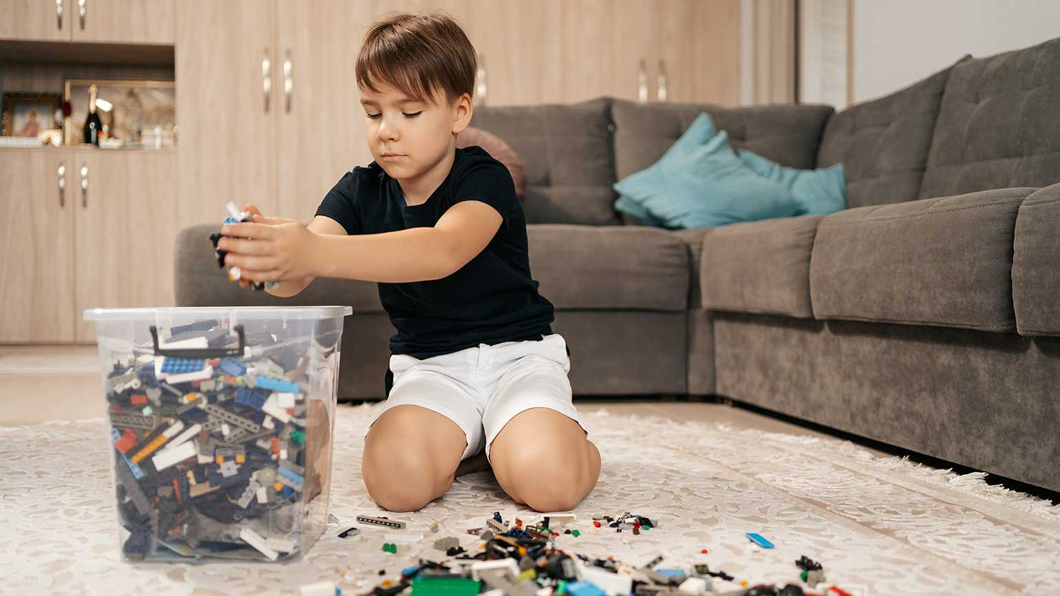 A young boy putting away his toys