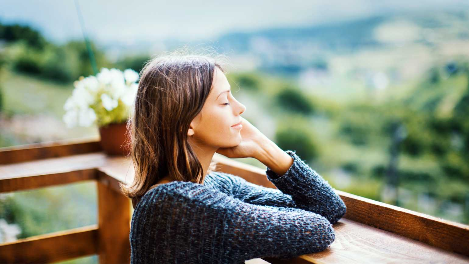 A woman in calm reflection outside.