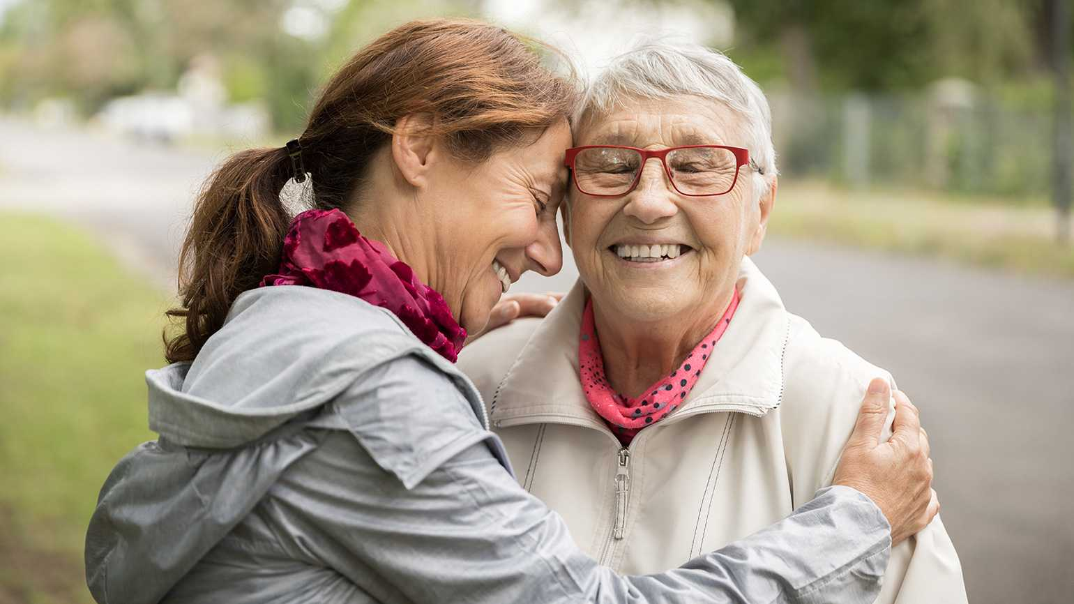 A caregiver embraces her mother
