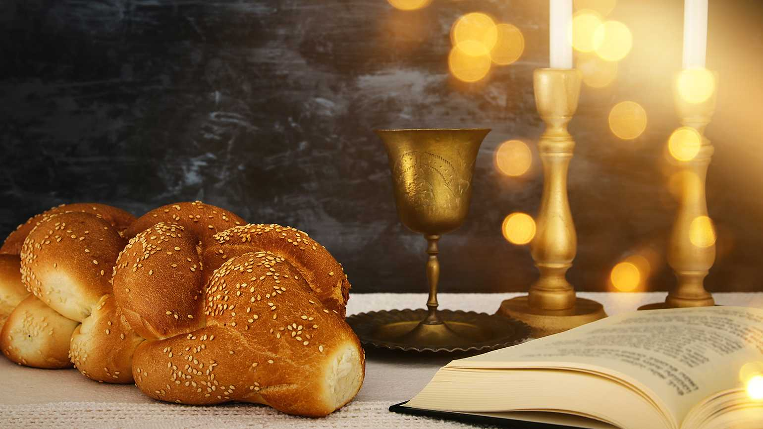Challah bread, wine and candles are placed on a table for Shabbat