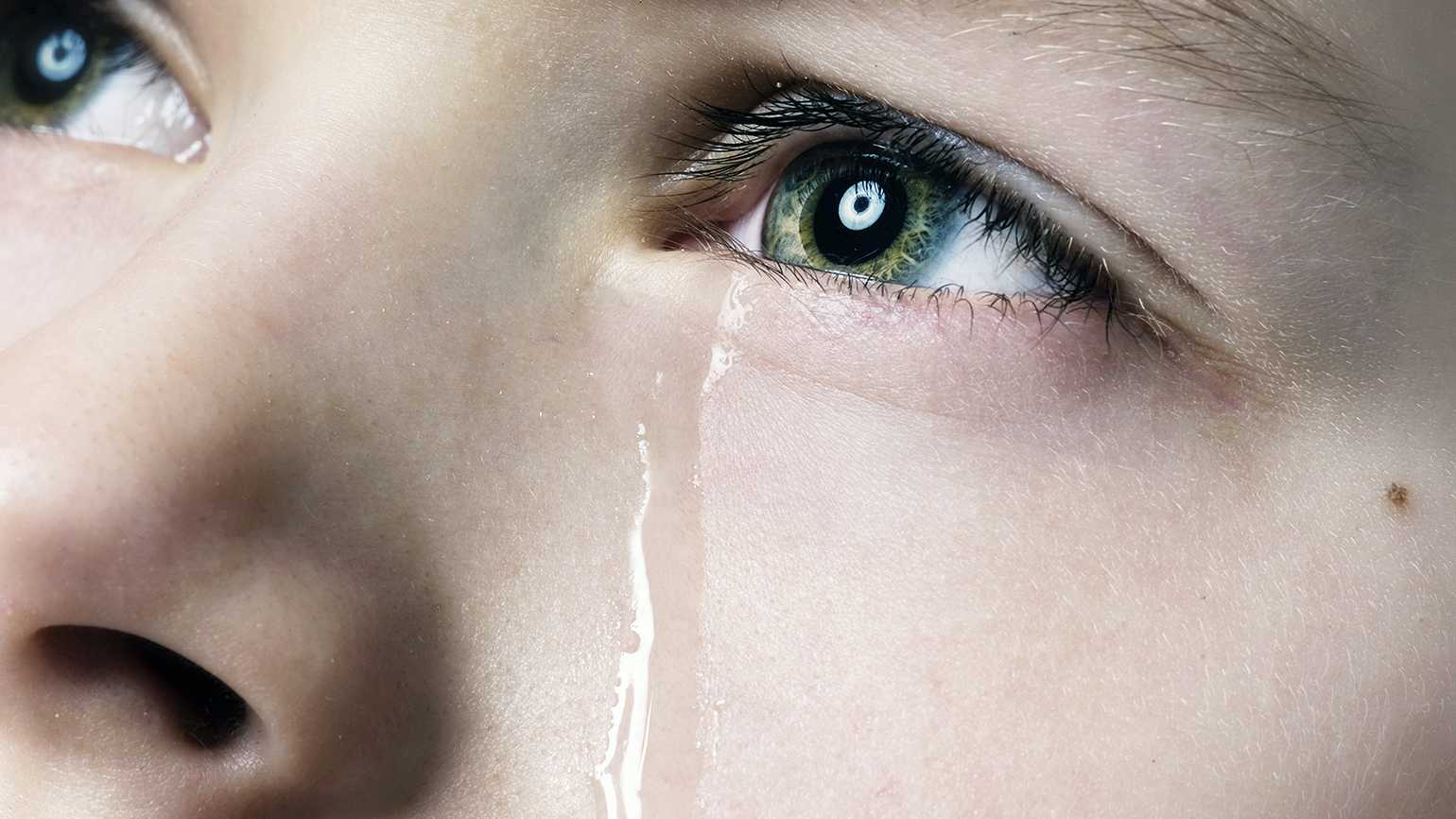 A young child sheds a tear