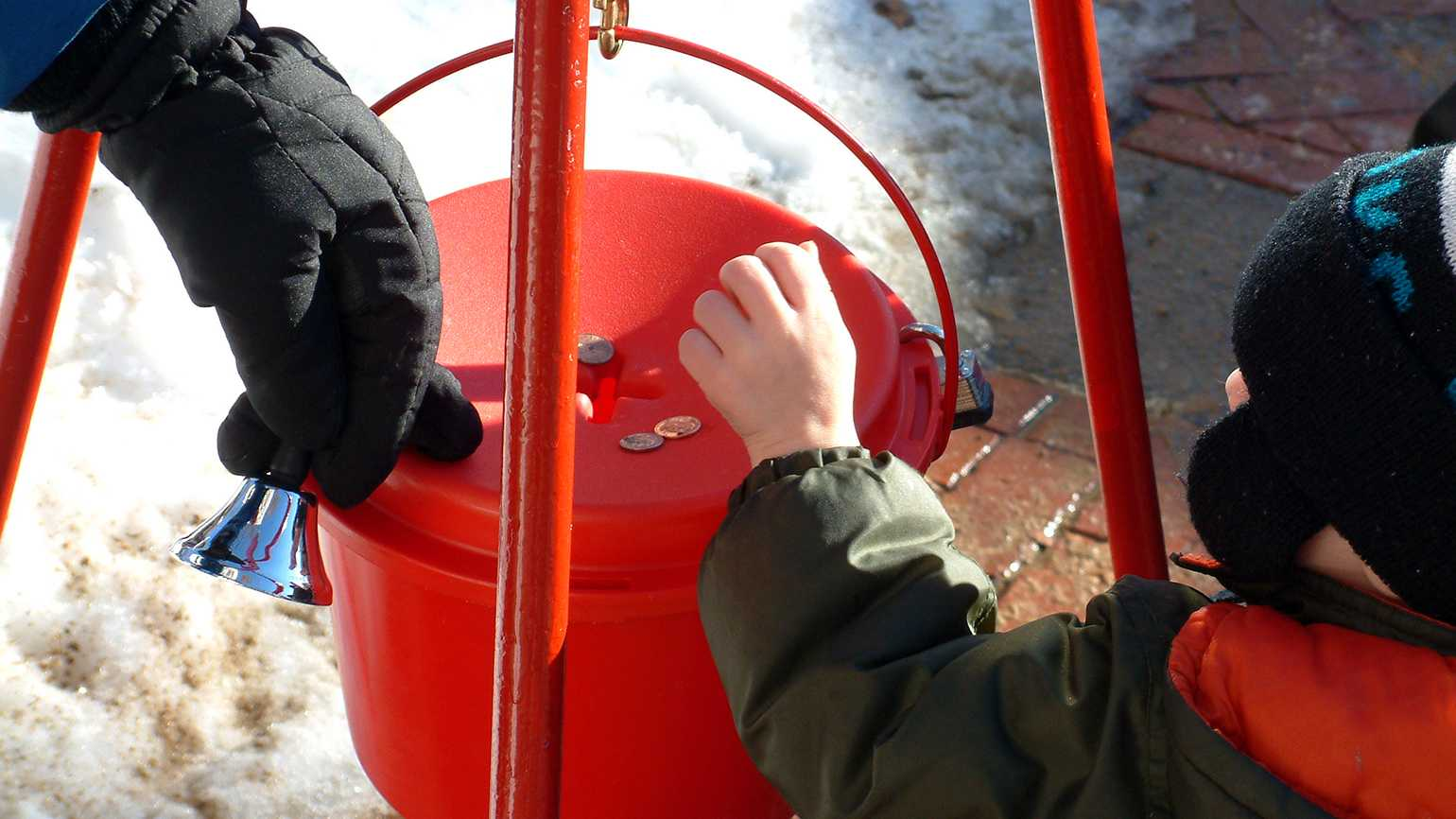 A child places money in a red charity bucket at Christmas