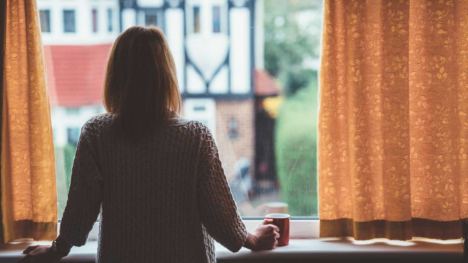 A woman having contemplative thoughts while looking out of her window.