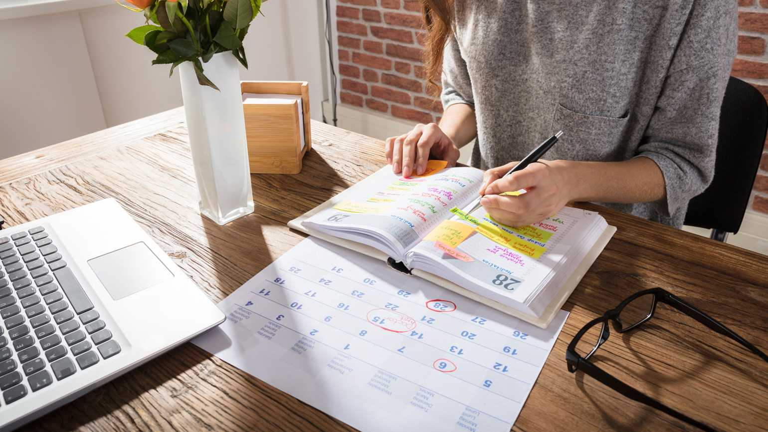 A woman organizing her day using an annual paper planner; Getty Images