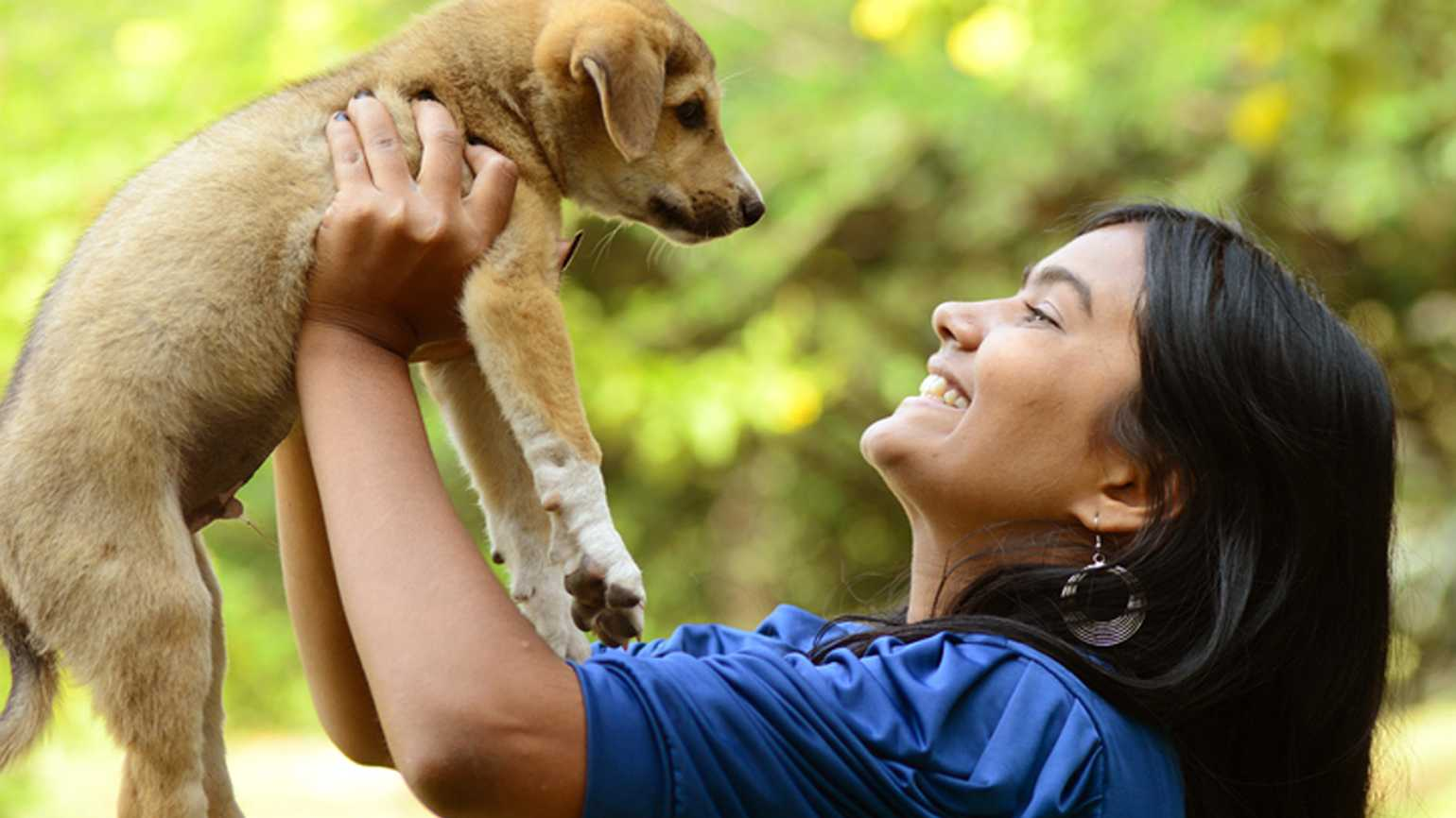 Woman lifts her newly adopted puppy in the air.