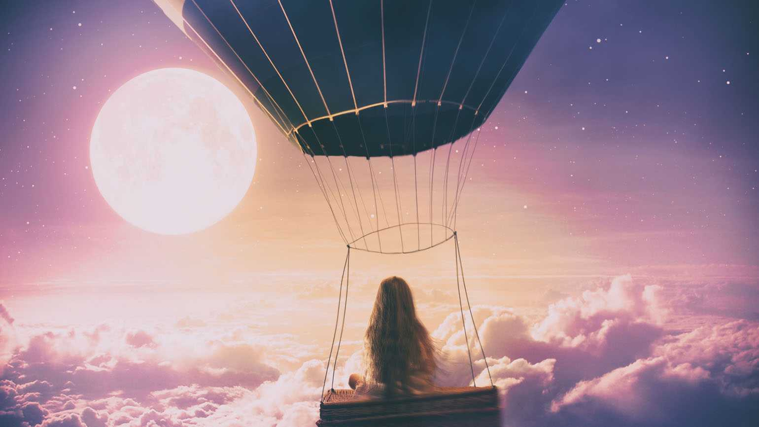 Young girl in a hot air balloon above clouds; Getty Images
