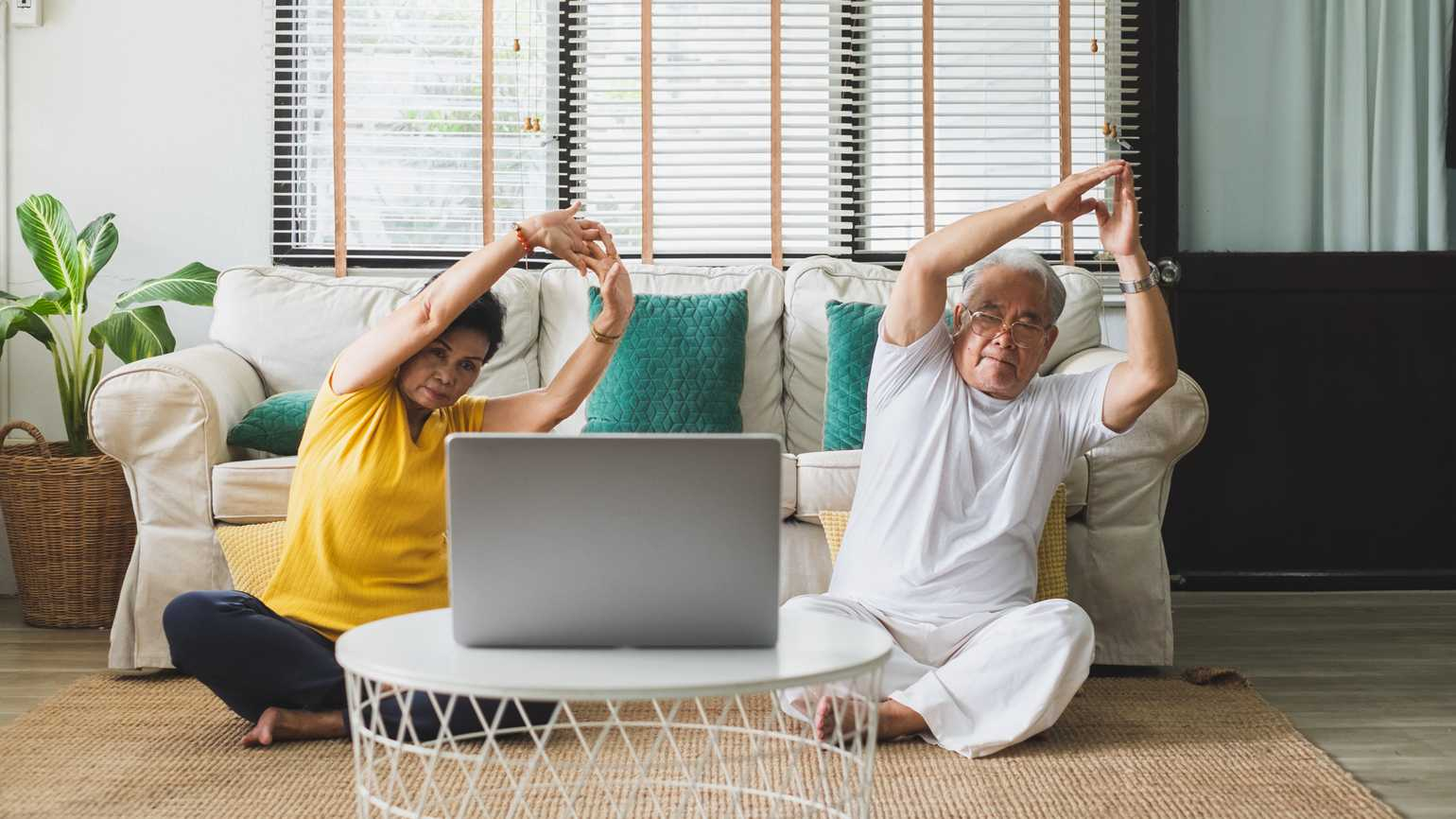 An elderly couple doing an at-home virtual exercise; Getty Images