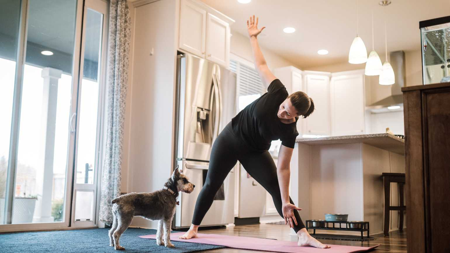 A woman exercising with her dog; Getty Images