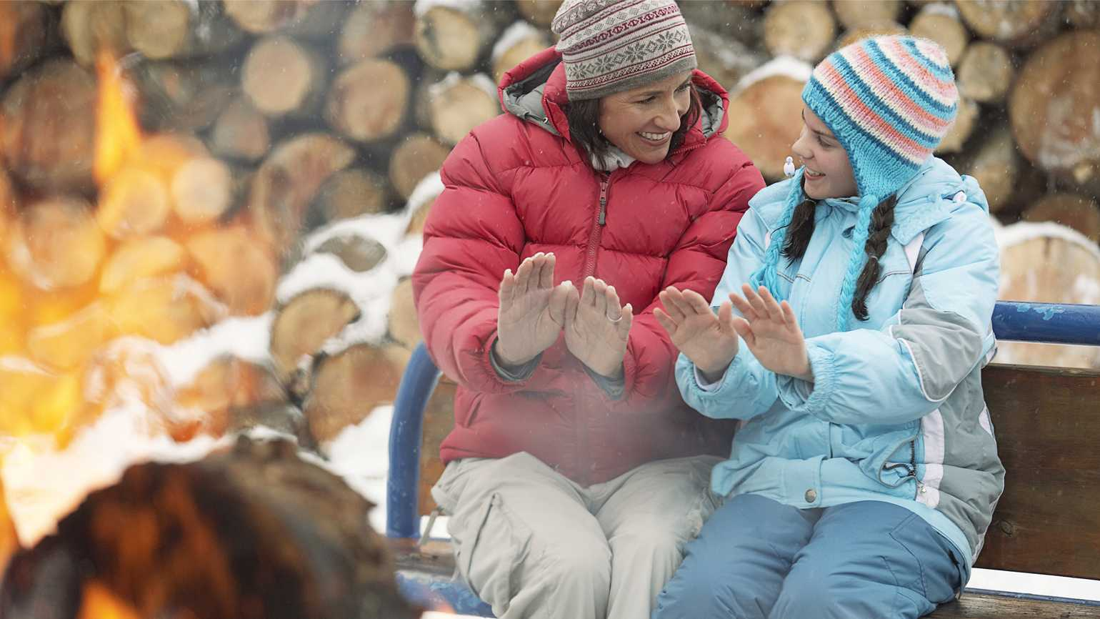 Mother and daughter enjoying a backyard fire pit; Getty Images